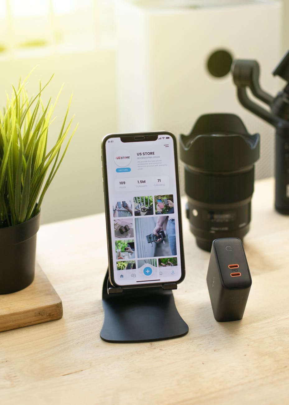 modern cellphone on holder placed on desk near gadgets