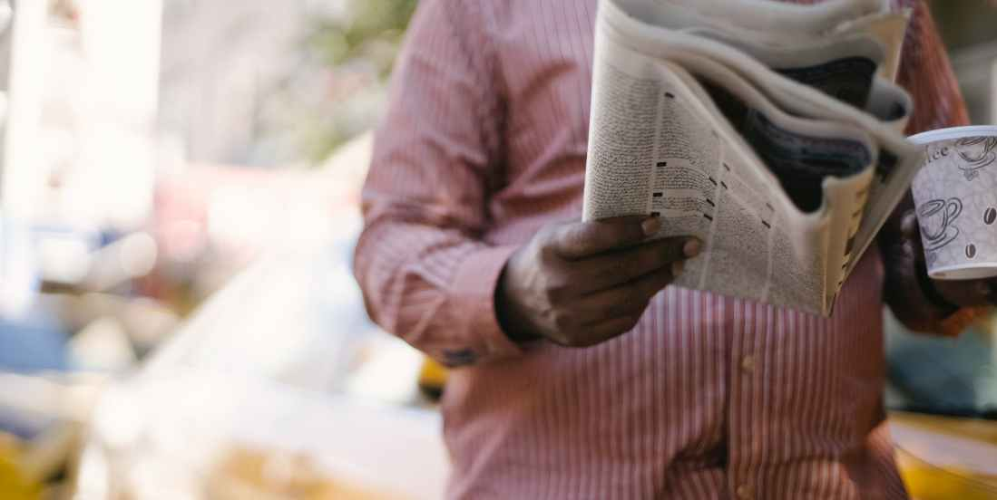 crop ethnic man with newspaper and coffee