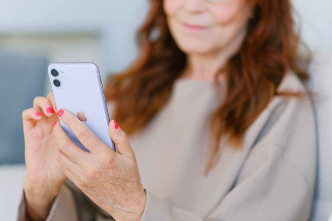 senior woman with red hair using contemporary smartphone