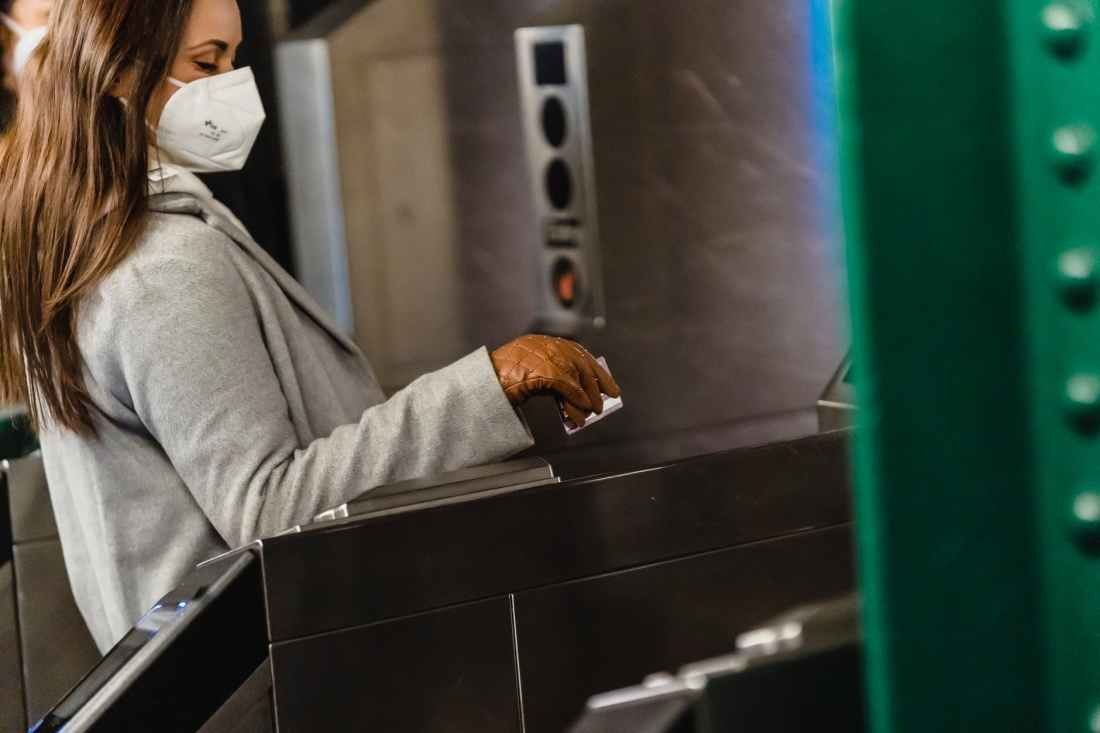 crop woman in mask passing through turnstile in metro