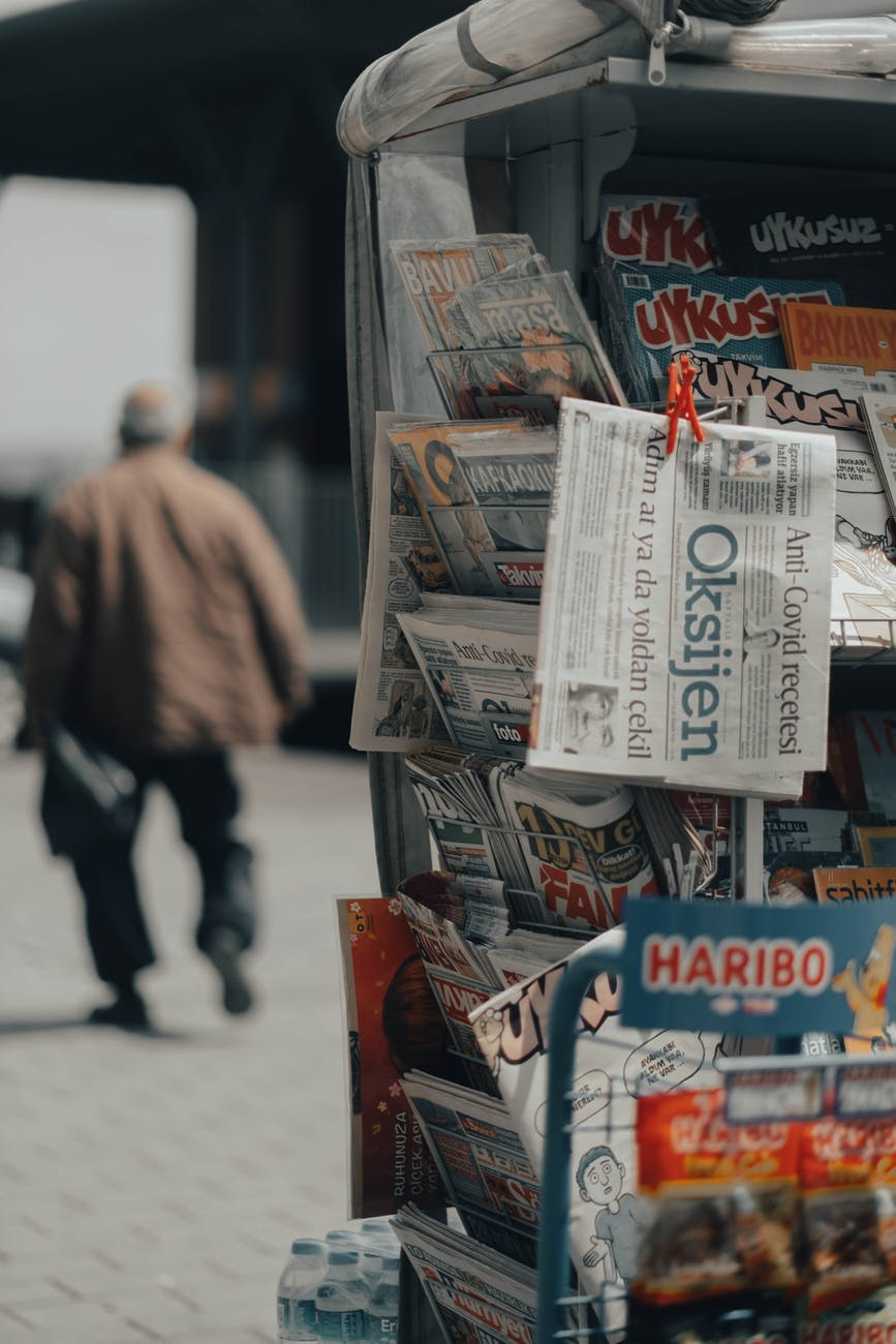 stand with newspapers in street on walkway near walking man