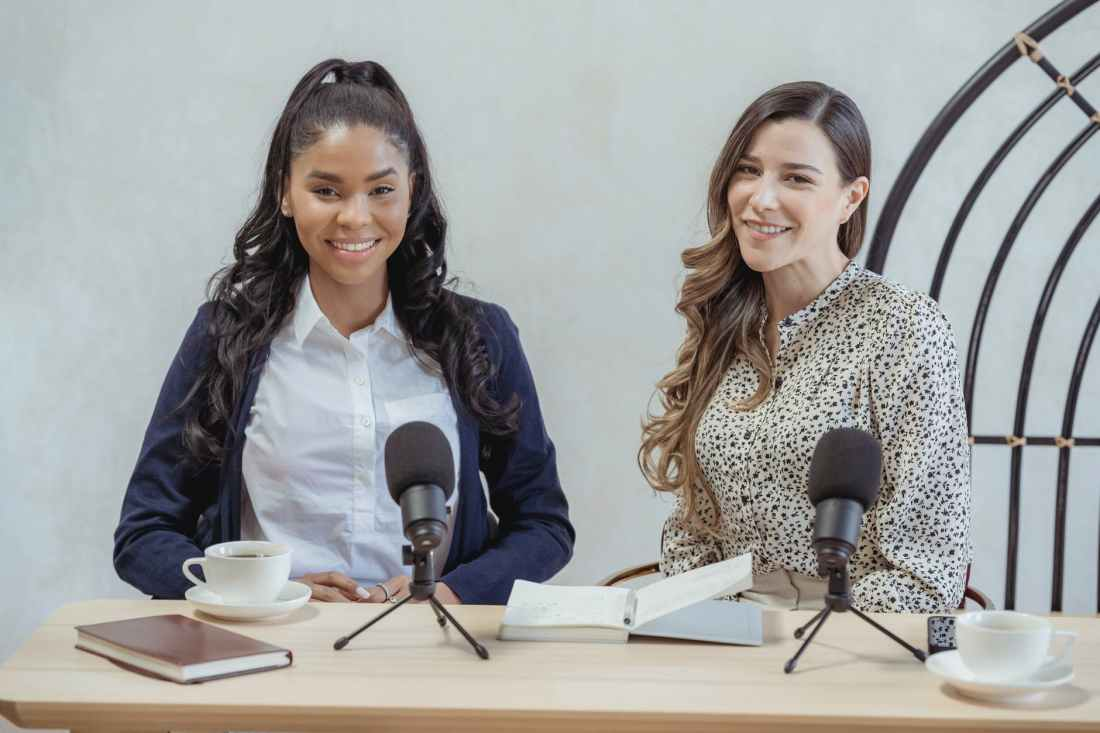 smiling diverse women sitting at desk with microphones